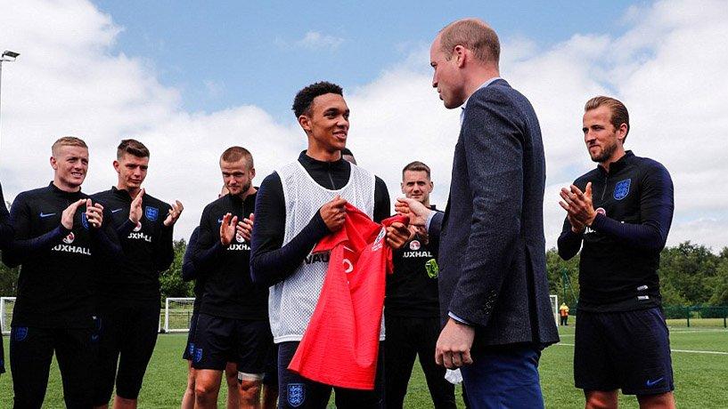 Prince William handing Trent Alexander-Arnold a jersey.