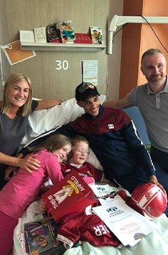 Alexander-Arnold gifted presents to a child in a hospital.