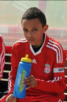 Trent Alexander-Arnold as a kid holding a water bottle in Liverpool uniform.