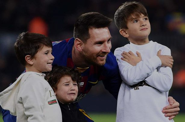 Three sons of Lionel Messi standing in a football field.